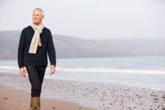 Homme supérieur marchant le long de la plage d'hiver Images stock