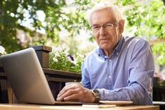 Homme supérieur moderne à l'aide de l'ordinateur portable en café extérieur photos libres de droits