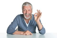 Homme supérieur montrant correct d'isolement sur le fond blanc Photographie stock libre de droits