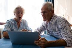 Homme supérieur montrant l'ordinateur portable à l'ami féminin dans la maison de repos Image stock