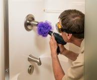 Homme supérieur nettoyant une douche avec le foret de puissance image stock