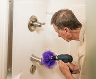Homme supérieur nettoyant une douche avec le foret de puissance image libre de droits