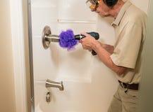 Homme supérieur nettoyant une douche avec le foret de puissance photographie stock libre de droits