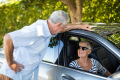 Homme supérieur parlant à la femme s'asseyant dans la voiture Photographie stock