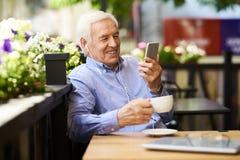 Homme supérieur parlant par l'appel visuel en café Images libres de droits