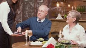 Homme supérieur payant la facture avec sa carte de crédit dans un restaurant photographie stock
