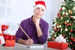 Homme supérieur pensant aux souhaits pour le Joyeux Noël Photographie stock libre de droits