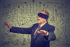 Homme supérieur plus âgé bandé les yeux d'affaires passant par des données sociales de media Photos stock