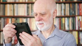 Homme supérieur plus âgé détendant à la maison lisant l'eBook appréciant la retraite Étagères à l'arrière-plan banque de vidéos