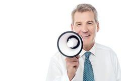 Homme supérieur posant avec le mégaphone Image libre de droits