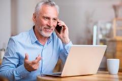 Homme supérieur positif parlant au téléphone portable Photos stock
