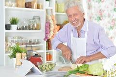 Homme supérieur préparant le dîner dans la cuisine Image stock