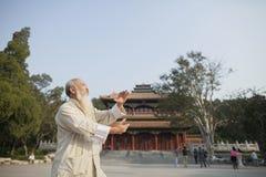 Homme supérieur pratiquant Tai Ji devant le bâtiment de chinois traditionnel Images stock
