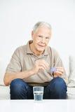 Homme supérieur prenant des pilules hors du récipient Photo libre de droits