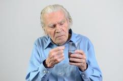 Homme supérieur prenant la dose prescrite de médecine Image stock
