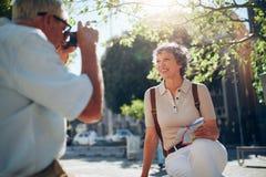 Homme supérieur prenant la photographie de vacances de son épouse Photographie stock libre de droits