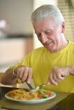 Homme supérieur prenant le petit déjeuner Image stock