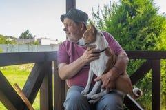 Homme supérieur prenant son beau chien de basenji et observant chacun des deux tout en se reposant sur la véranda d'été Images libres de droits