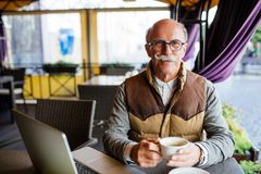 Homme supérieur réfléchi avec la tasse de café se reposant au café dans la ville Image libre de droits