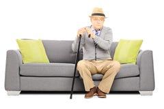 Homme supérieur réfléchi avec une canne se reposant sur un sofa Photo stock