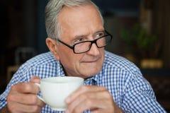 Homme supérieur réfléchi s'asseyant au café Image stock