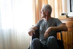 Homme supérieur réfléchi s'asseyant sur le fauteuil roulant dans la maison de repos Photos libres de droits