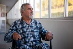 Homme supérieur réfléchi s'asseyant sur le fauteuil roulant dans la maison de repos Photo stock
