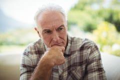 Homme supérieur réfléchi s'asseyant sur le sofa dans le salon Image libre de droits