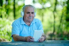 Homme supérieur recherchant un air sur son lecteur MP3 Photographie stock libre de droits