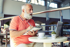 Homme supérieur regardant l'ordinateur portable et l'inscription Photos libres de droits