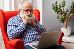 Homme supérieur regardant l'ordinateur portable et le sondage à la maison Image stock