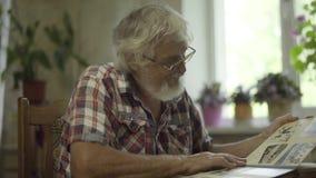 Homme supérieur regardant par l'album avec ses vieilles photos clips vidéos
