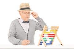 Homme supérieur regardant un abaque posé à la table Photos libres de droits