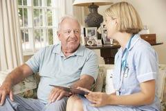 Homme supérieur retiré ayant le contrôle de santé avec l'infirmière At Home image libre de droits