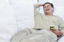 Homme supérieur riant tandis que musique de écoute Photographie stock libre de droits