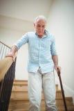 Homme supérieur s'élevant en bas avec le bâton de marche Photo stock