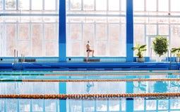 Homme supérieur s'étirant par la piscine d'intérieur Image stock
