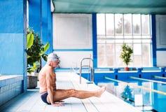 Homme supérieur s'étirant par la piscine d'intérieur Photographie stock libre de droits