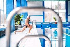 Homme supérieur s'étirant par la piscine d'intérieur Photo libre de droits