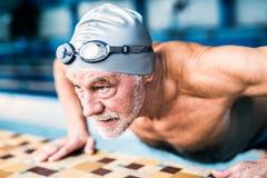 Homme supérieur s'étirant par la piscine d'intérieur Photos libres de droits