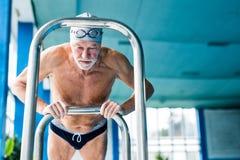 Homme supérieur s'étirant par la piscine d'intérieur Images stock