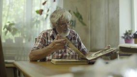 Homme supérieur s'asseyant à la maison et regardant son vieil album avec des photos clips vidéos