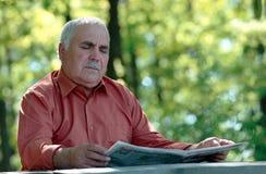 Homme supérieur s'asseyant lisant un journal Images stock