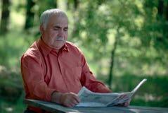 Homme supérieur s'asseyant lisant un journal Photographie stock