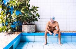 Homme supérieur s'asseyant par la piscine d'intérieur Image stock