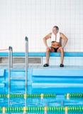 Homme supérieur s'asseyant par la piscine d'intérieur Photos libres de droits