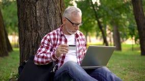 Homme supérieur s'asseyant sur l'herbe et les billets de réservation en ligne, mâle se reposant en parc photos libres de droits