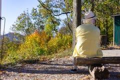homme supérieur s'asseyant sur le banc à l'automne de dessus de montagne image stock