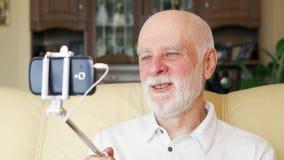 Homme supérieur s'asseyant sur le divan à la maison ayant la causerie visuelle Professeur parlant sur le mobile par l'intermédiai banque de vidéos