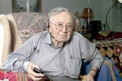 Homme supérieur s'asseyant sur le divan avec l'écouteur Photos stock